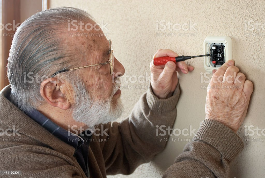 Senior adult fixing an outlet. stock photo