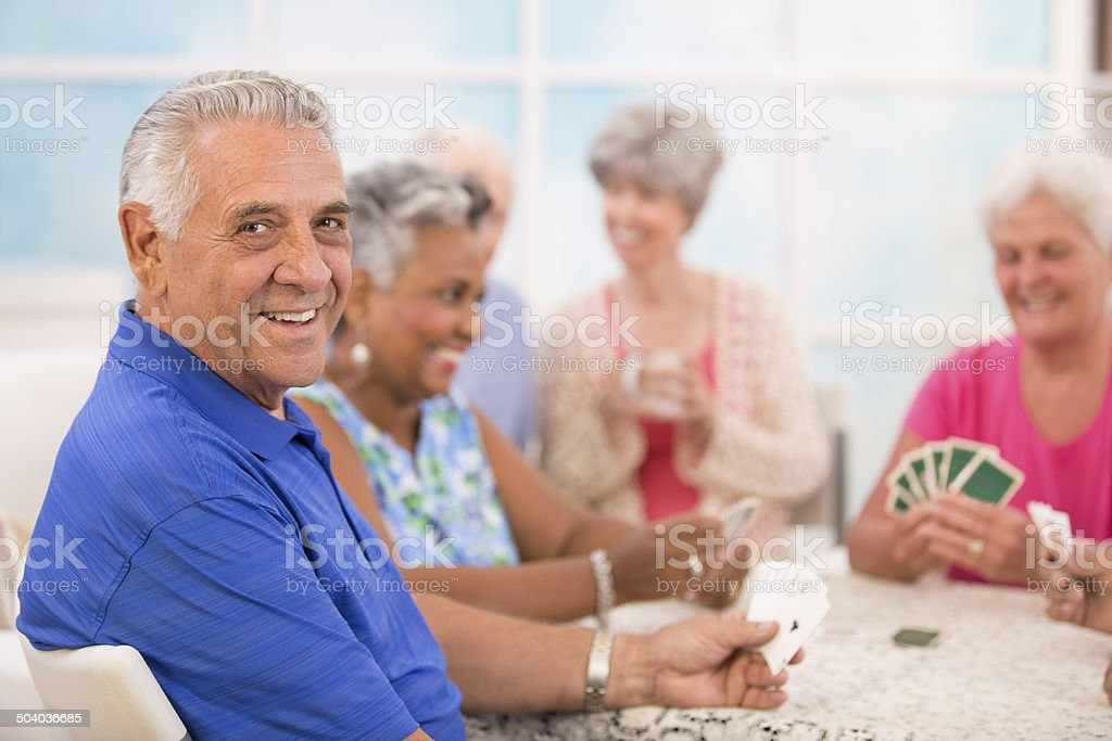 Senior adult friends playing cards. Home or community center setting. stock photo