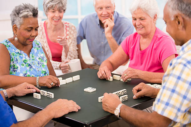 Senior adult friends playing dominoes. Home or community center setting. stock photo