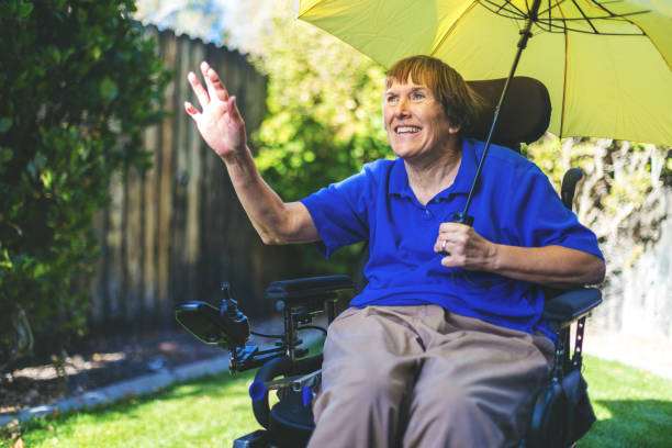 Senior Adult happy Female with physical disability of multiple sclerosis outside waving and holding umbrella in front yard in Western Colorado stock photo