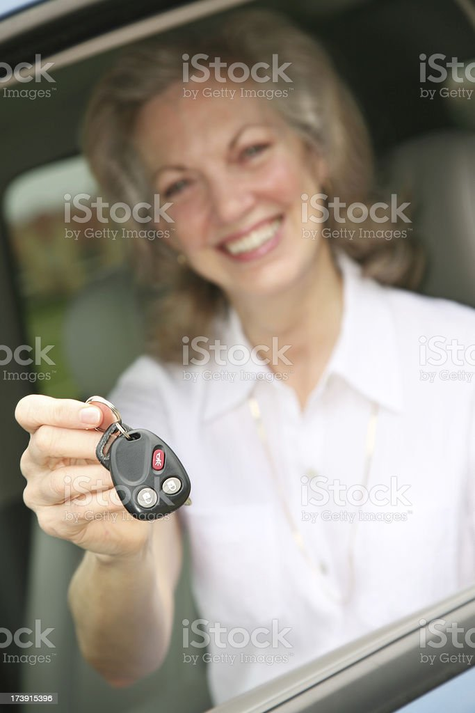 Senior Adult Holding out Car Keys, Key in Focus royalty-free stock photo
