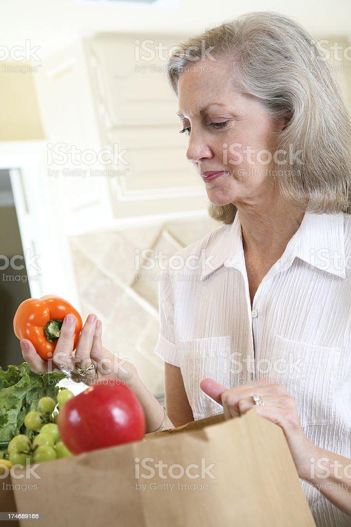 Senior Adult Homemaker Inspecting Orange Pepper in Her Groceries royalty-free stock photo