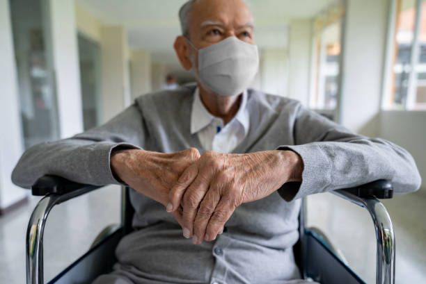 Senior adult in a wheelchair at the hospital wearing a facemask stock photo