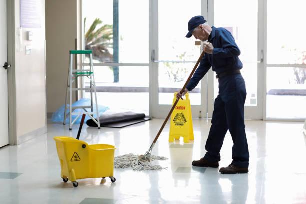 senior adult janitor mops boden bei der einfahrt in die büros. - hausmeister stock-fotos und bilder