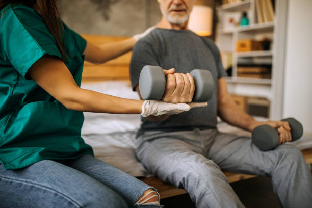 Senior adult man and home healthcare nurse, physical therapist stock photo