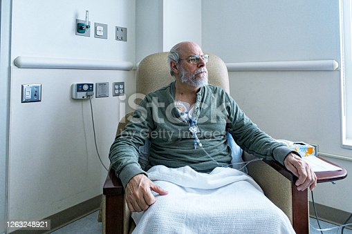 A recovering senior adult man colorectal cancer patient is sitting resting comfortably in a hospital cancer ward easy chair while chemotherapy IV drip medicine is administered by an array of medical equipment through a subcutaneous intravenous chemo access port temporarily embedded into his upper chest.