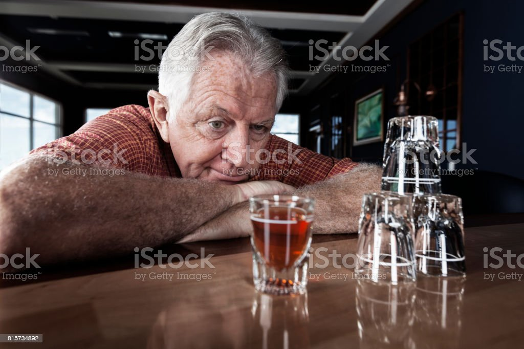 A senior adult man contemplates on taking another drink at a bar stock photo