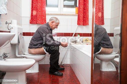Senior Adult Man Defecating in Domestic Bathroom.