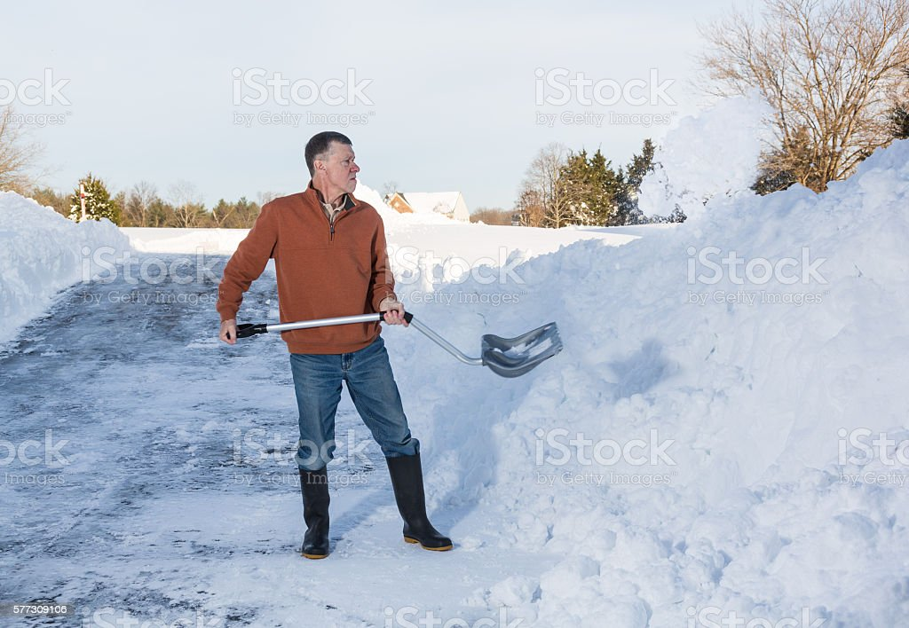 Senior adult man finishes digging out drive in snow stock photo