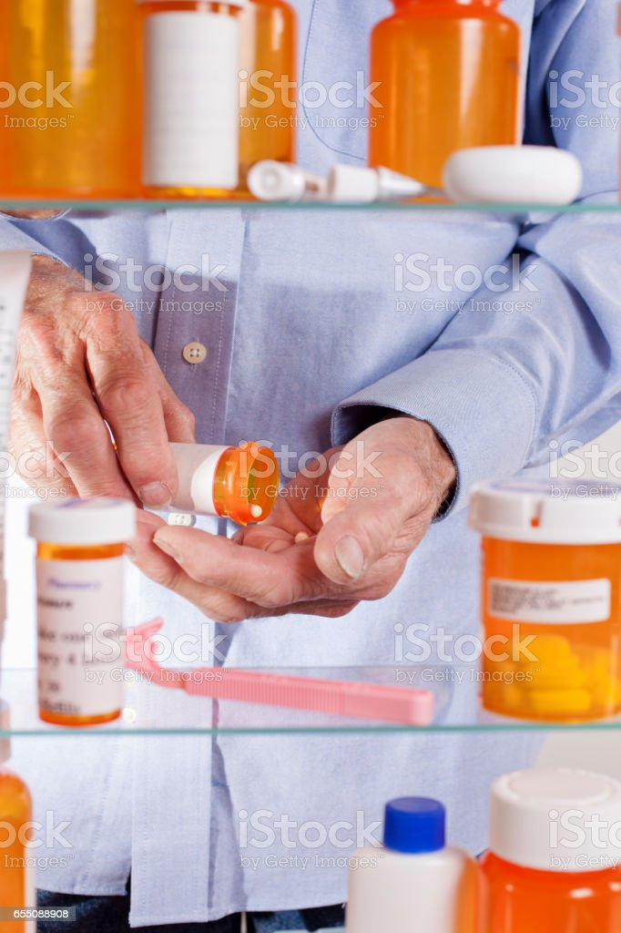 Senior adult man gets prescription medicines out of cabinet. stock photo