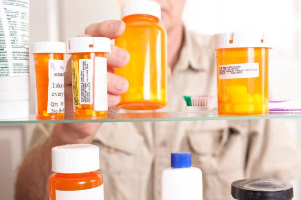 Senior adult man gets prescription medicines out of cabinet. stock photo