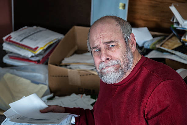 senior adult man hoarder in messy office room - hoarding stock photos and pictures