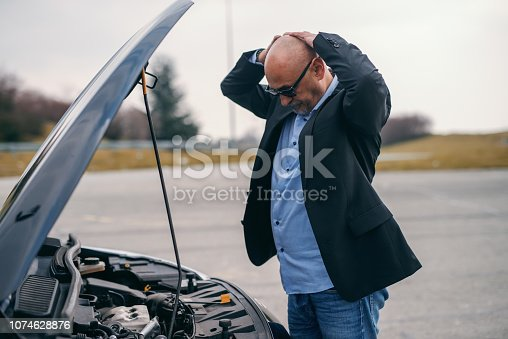 istock Senior adult man holding hands on head while standing in front of opened hood of his car. 1074628876
