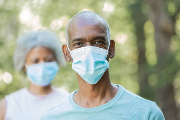 Senior adult man is wearing  a surgical mask outdoors stock photo