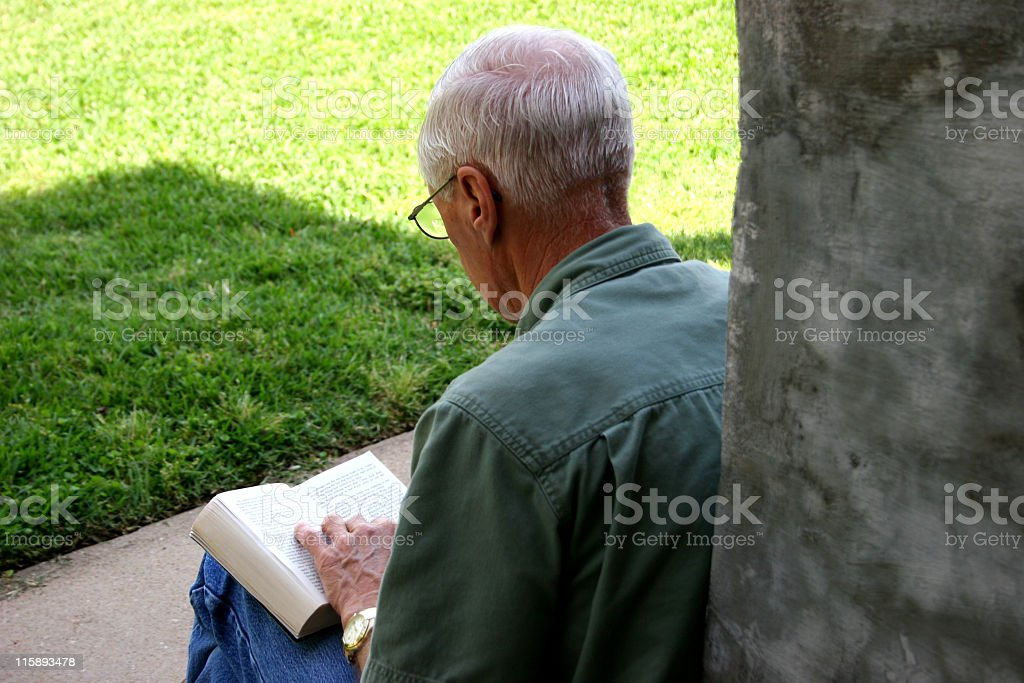 Senior adult man reading book on front porch steps. Outdoors. royalty-free stock photo
