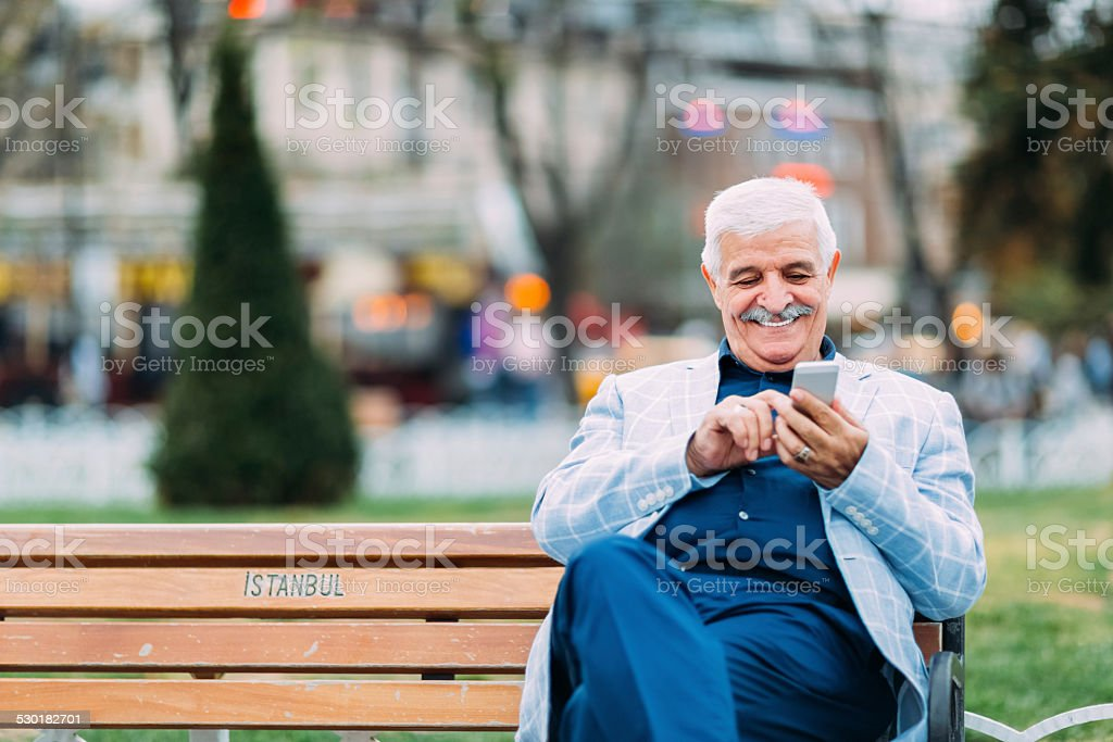 Senior adult man texting while resting outside stock photo