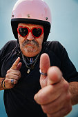 Senior adult man wearing pink helmet and heart shape sunglasses from his granddaughter, isolated on blue wall background