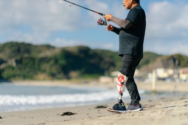 ビーチで人工脚釣りを持つシニア大人の男性 - real bodies ストックフォトと画像