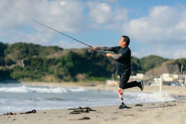 ビーチで人工脚釣りを持つシニア大人の男性 - disabilitycollection ストックフォトと画像