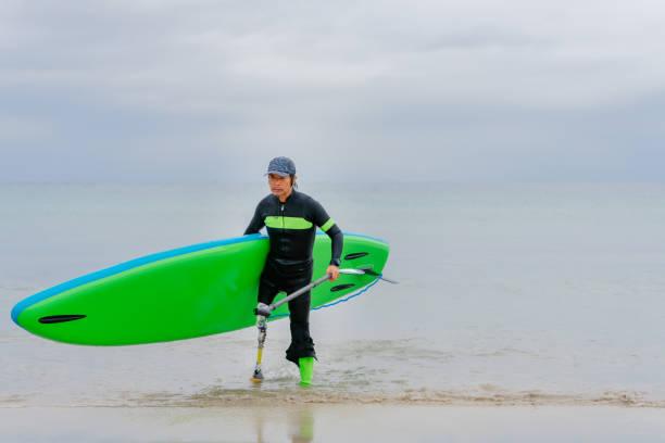 パドルボードを持ち、海から歩く人工脚を持つシニアアダルト男性 - real bodies ストックフォトと画像