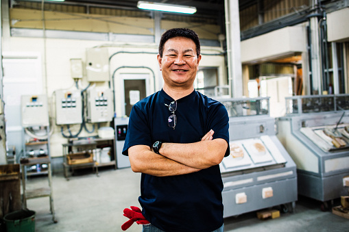 istock Senior adult man working in glass factory 693959616