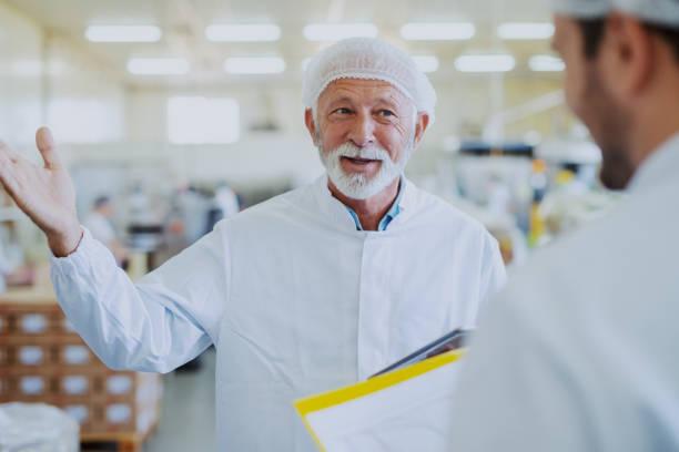 senior adult manager praten met medewerker over de kwaliteit van voedsel. beide gekleed in steriele uniformen. voedselplant interieur. - netherlands map stockfoto's en -beelden