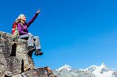 Female hiker sitting on a rock high in the European Alps above Zermatt.