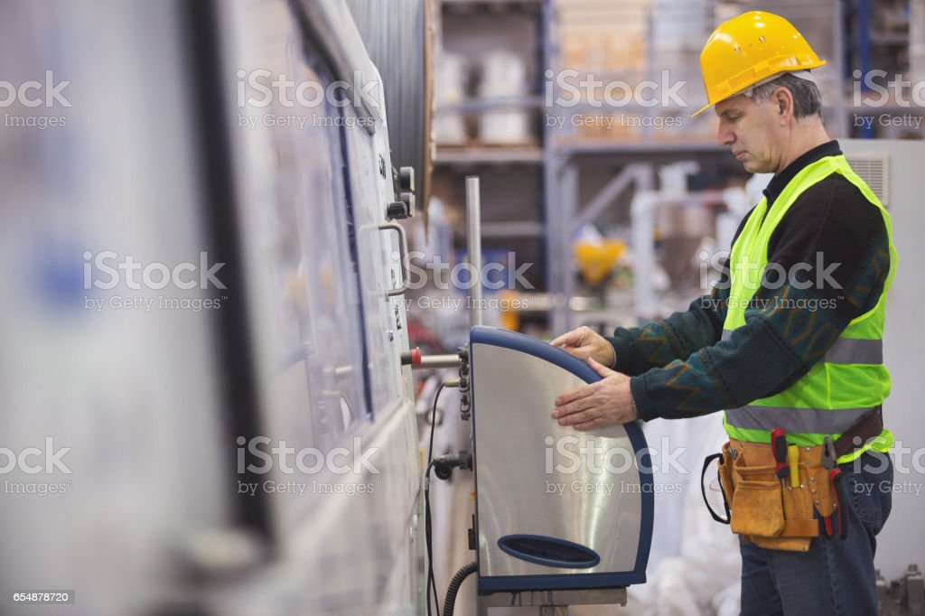 Senior adult operating a machine in factory stock photo