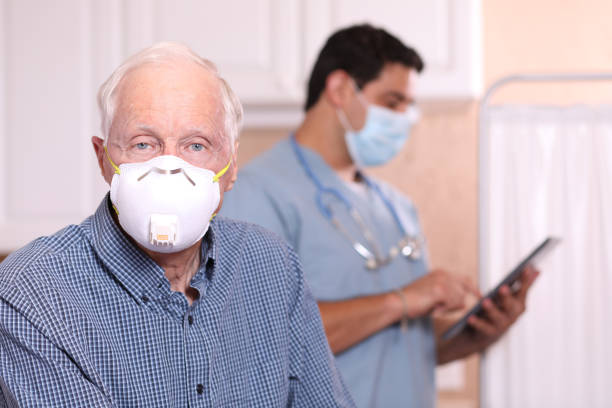 COVID-19: Senior adult patient, N95 face mask, doctor office. Latin descent doctor or healthcare worker, consultation with senior adult patient in office, hospital, or clinic setting.  Senior man wears N95 face mask. Doctor background. Coronavirus, medical exam, consultation. covid stock pictures, royalty-free photos & images