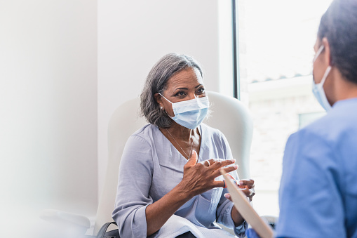A senior female patient gestures while describing her symptoms to a female healthcare provider. The patient and doctor are wearing protective face coverings.