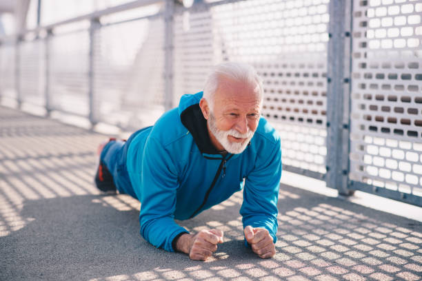 A senior adult planking outdoors. He is wearing blue sports clothing. It's a sunny day. stock photo