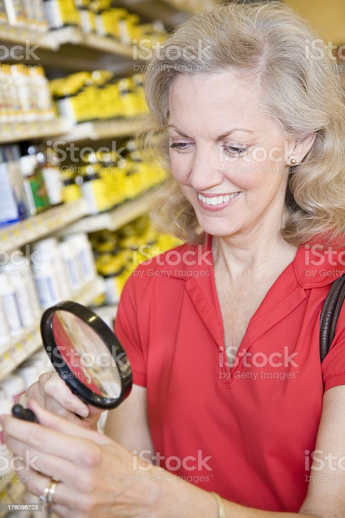Senior Adult Reading Medicine Bottle with Magnifying Glass royalty-free stock photo