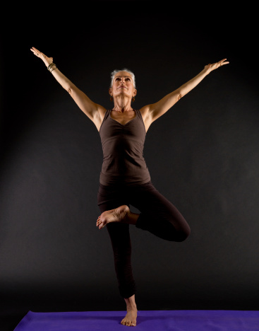 senior adult standing in a yoga pose stock photo