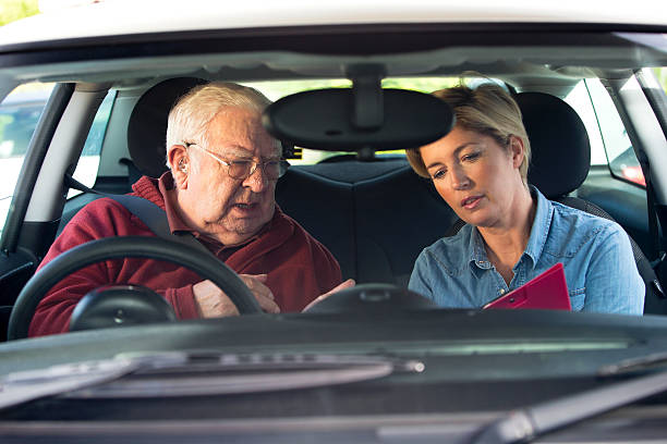 Senior Adult taking Driving Lessons Senior man in a car with driving instructor taking lessons driving instructor stock pictures, royalty-free photos & images