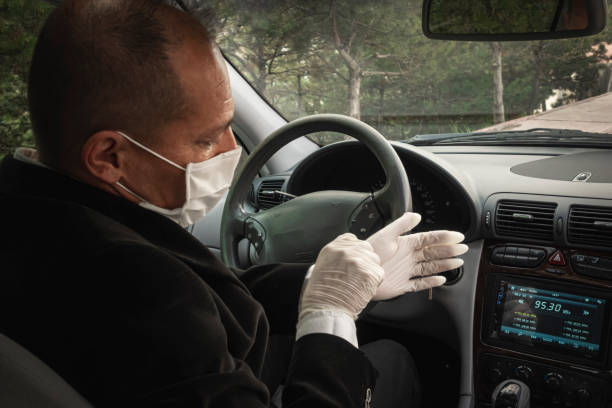 A senior adult trying to wear his surgical gloves in his car for protection stock photo