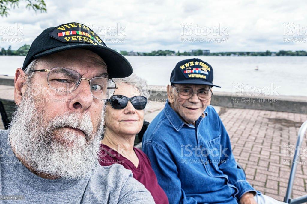 Senior Adult USA Military Veterans Family Sitting at the Lake - Foto stock royalty-free di 60-69 anni