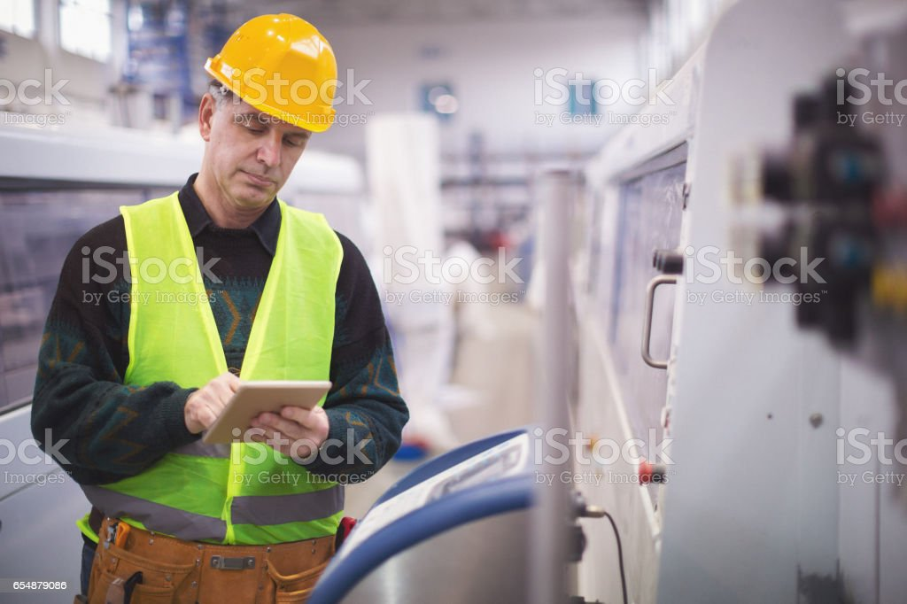 Senior adult using tablet pc in factory stock photo