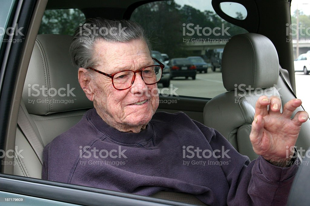 Senior adult waving from the car window. royalty-free stock photo