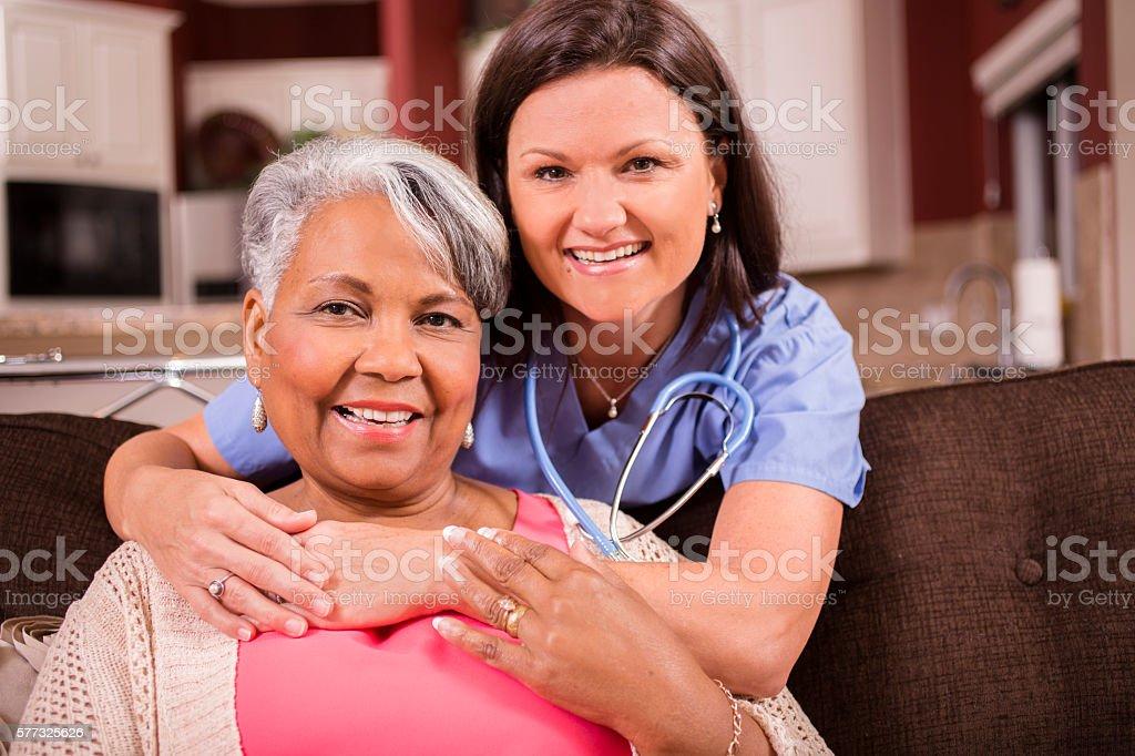 African descent, female senior adult enjoys hugs from her home...