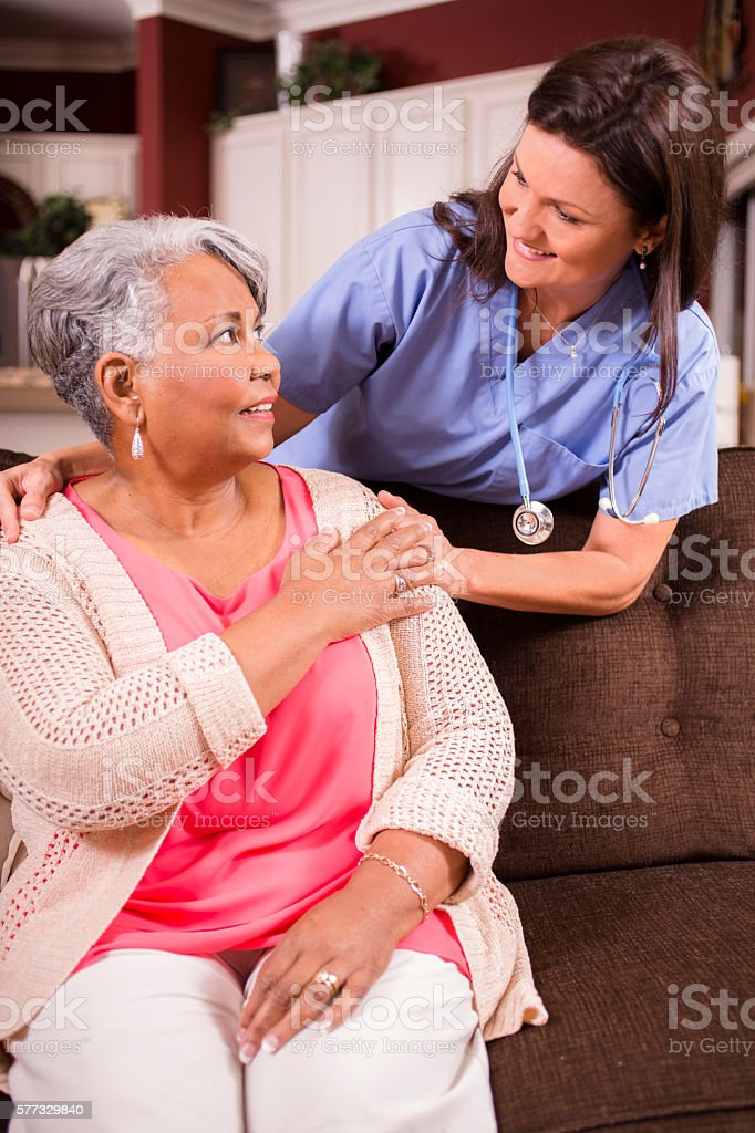 Senior adult with home healthcare nurse, caregiver at home. stock photo