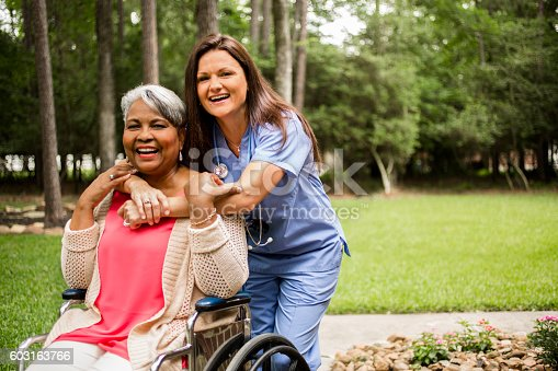 istock Senior adult with home healthcare nurse, caregiver outdoors. 603163766