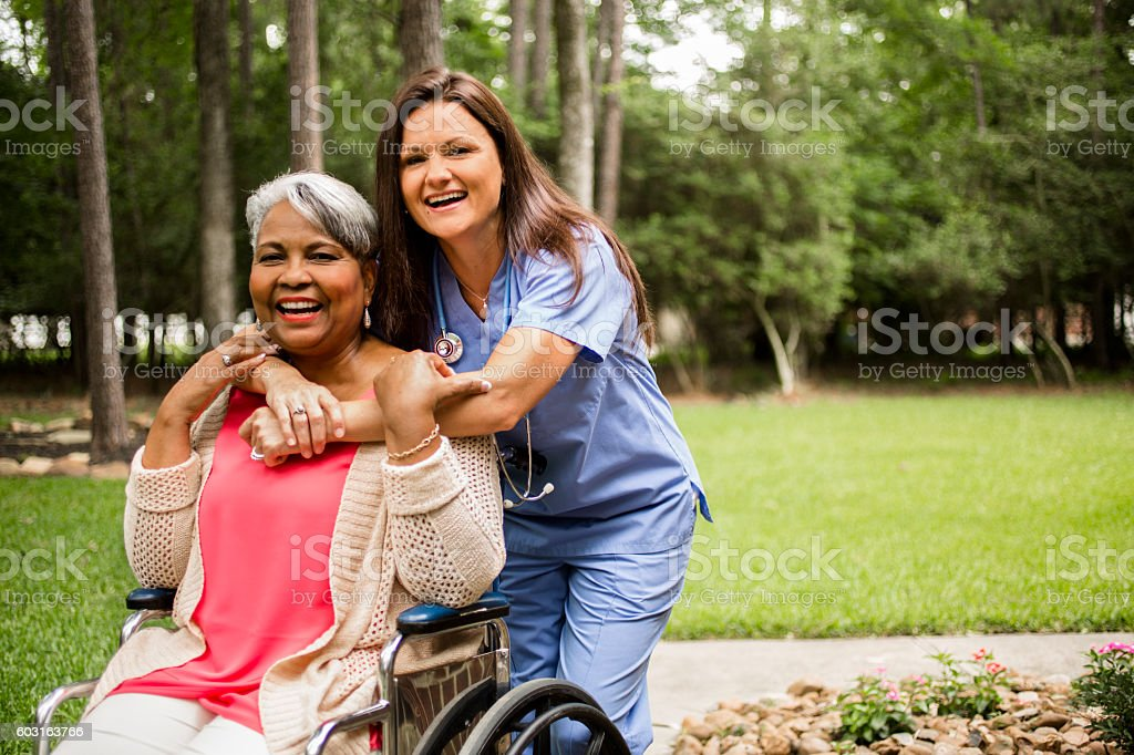 Senior adult with home healthcare nurse, caregiver outdoors. stock photo