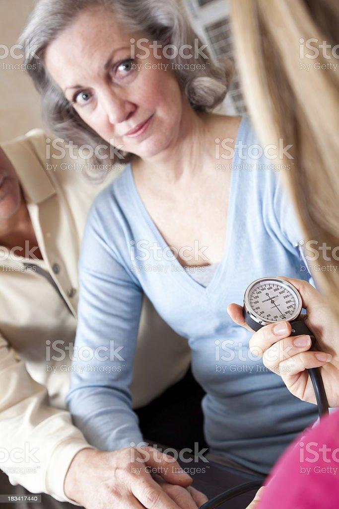 Senior Adult With Husband Having Blood Pressure Taken By Nurse royalty-free stock photo