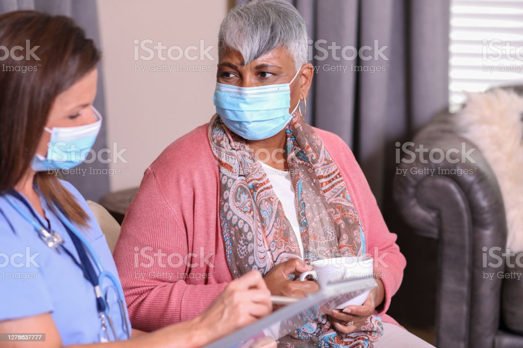Senior adult woman and home health care nurse. Senior adult, African descent patient and her home health care nurse.  They have been discussing treatment options in assisted living or at-home setting. Adult Stock Photo