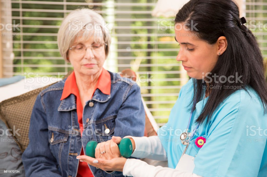 Senior adult woman and home healthcare nurse, physical therapist. stock photo