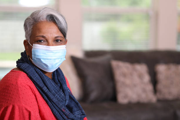 Senior adult woman at home wearing face mask for COVID-19. African descent, senior adult woman at home.  She is sitting on her living room sofa wearing a face mask to protect herself from COVID-19. covid-19 stock pictures, royalty-free photos & images