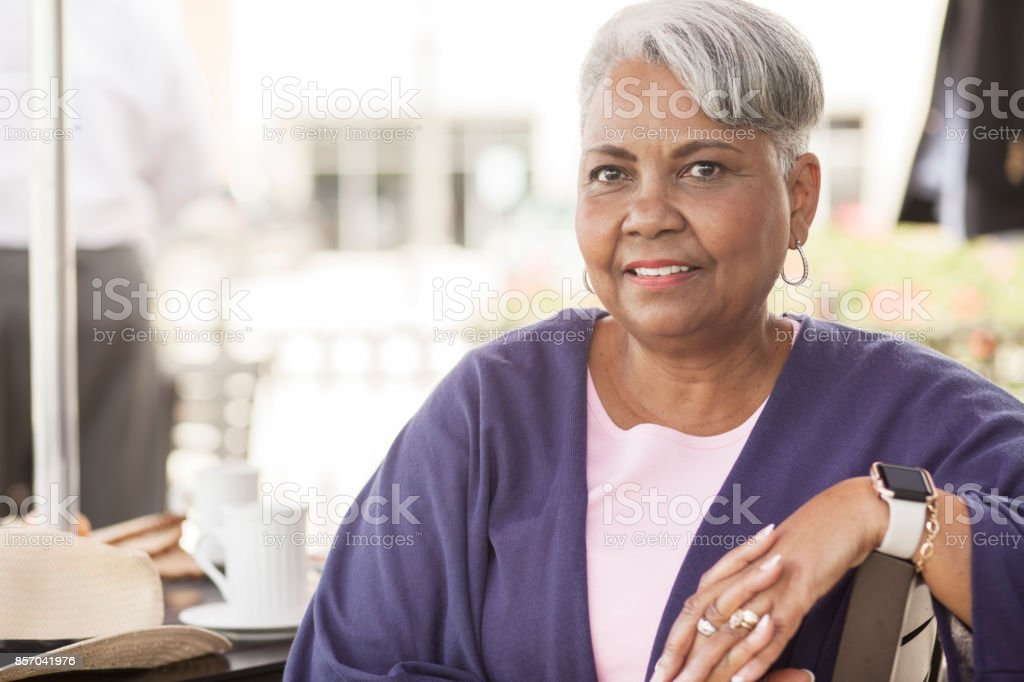 Senior adult woman dining at outdoor cafe. stock photo