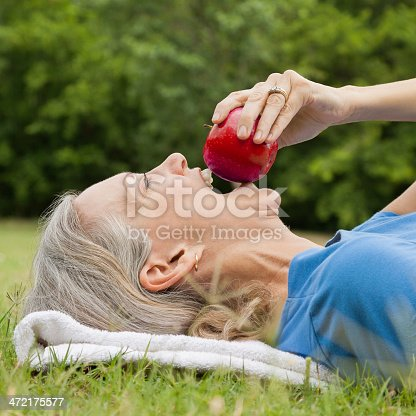 istock Senior adult woman eating a red apple on the grass 472175577