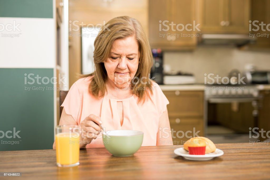 Senior adult woman forced to eat stock photo