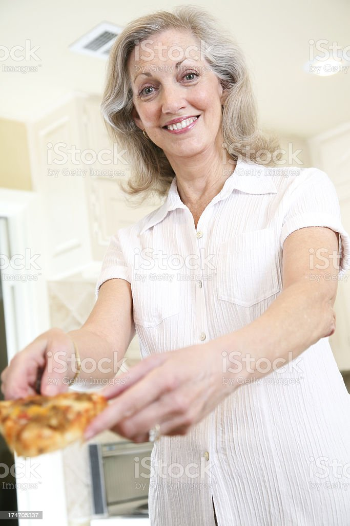Senior Adult Woman Happily Serving A Slice of Pizza royalty-free stock photo